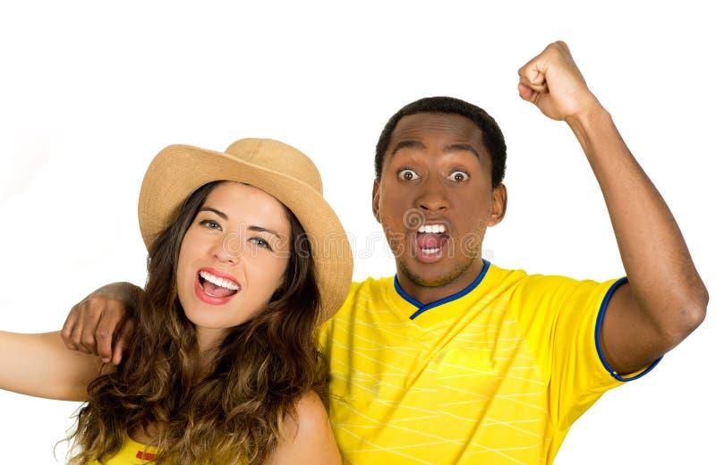 Γοητευτικός το διαφυλετικό ζεύγος που φορά τα κίτρινα πουκάμισα ποδοσφαίρου ενθαρρυντικά χαρωπά στη κάμερα, άσπρο υπόβαθρο στούντ στοκ φωτογραφίες με δικαίωμα ελεύθερης χρήσης