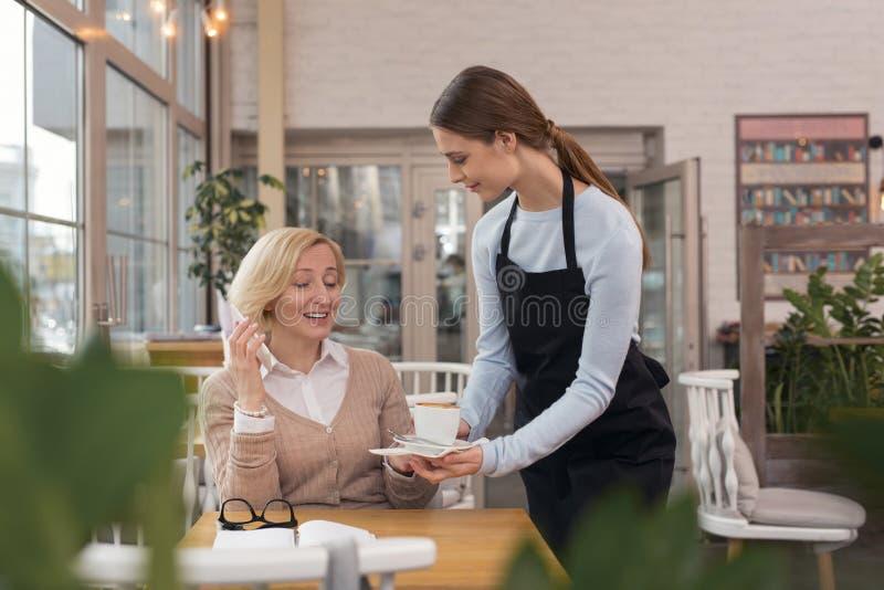 Γοητευτικός φέρνοντας καφές σερβιτορών στον πελάτη της στοκ φωτογραφία