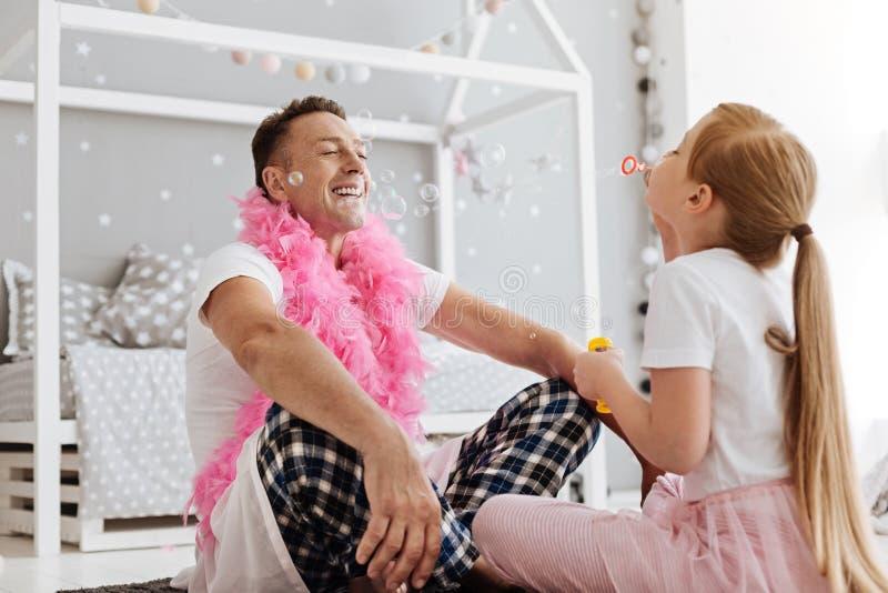Γοητευτικό αρχικό κορίτσι που κάνει το γέλιο μπαμπάδων της στοκ εικόνες