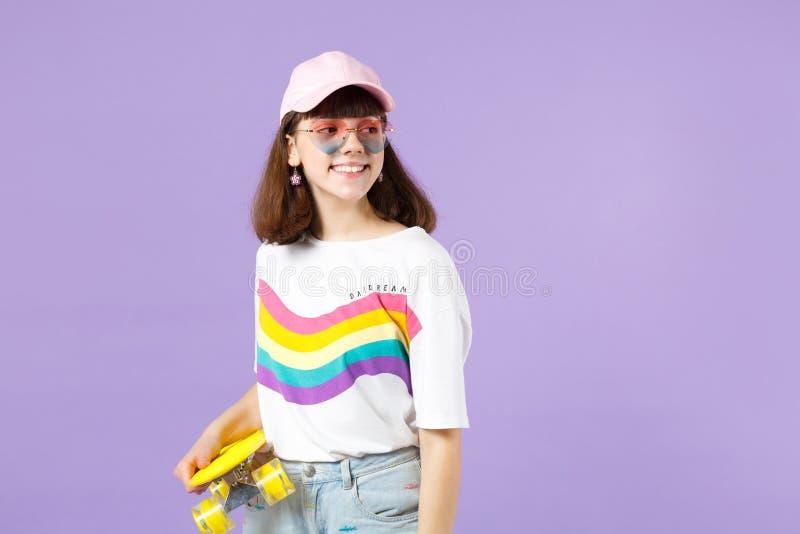 Γοητευτικό κορίτσι εφήβων στα ζωηρά ενδύματα, eyeglasses καρδιών που κρατά κίτρινο skateboard κατά μέρος απομονωμένος στην ιώδη κ στοκ εικόνα με δικαίωμα ελεύθερης χρήσης