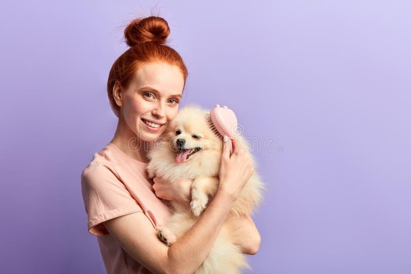 Γοητευτικό κορίτσι με το οδοντωτό χαμόγελο που χρησιμοποιεί τη βούρτσα για να φροντίσει το λατρευτό κατοικίδιο ζώο της στοκ εικόνα