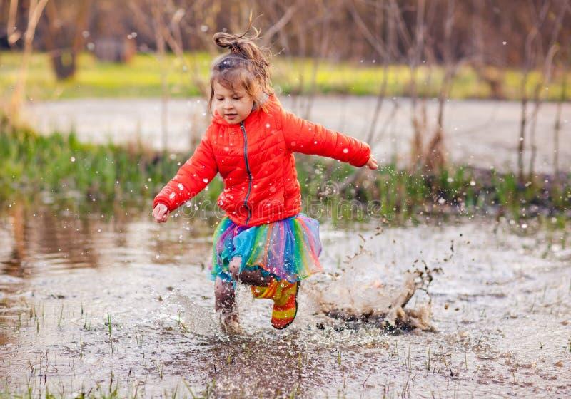 Γοητευτικό κορίτσι που τρέχει στη μεγάλη λακκούβα στοκ εικόνα