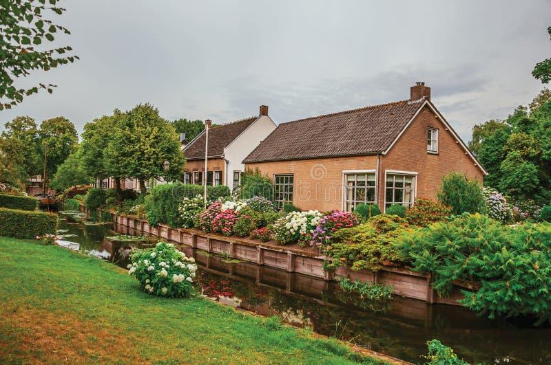 Γοητευτικό μικρό κανάλι δίπλα στα αγροτικά σπίτια με τον πολύβλαστους flowery κήπο και το χορτοτάπητα στη νεφελώδη ημέρα σε Drimm στοκ εικόνες