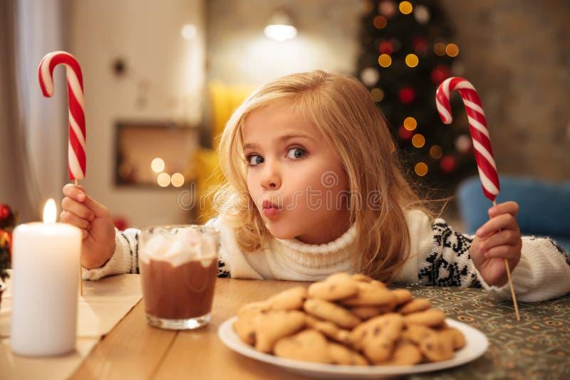 Γοητευτικό μικρό κορίτσι με δύο καλάμους καραμελών ενώ έχοντας εορταστικό στοκ εικόνες