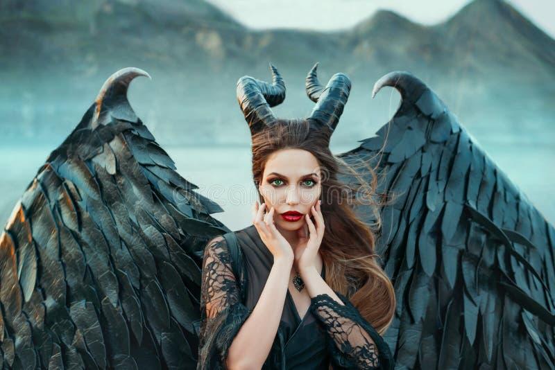 Γοητευτικό πορτρέτο του σκοτεινού αγγέλου με τα αιχμηρά κέρατα και τα νύχια στα ισχυρά ισχυρά φτερά, κακή μάγισσα στο μαύρο φόρεμ στοκ φωτογραφία με δικαίωμα ελεύθερης χρήσης