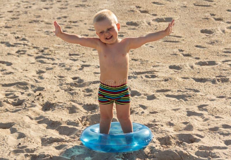 Γοητευτικό χαμογελώντας αγόρι και lifebuoy στην άμμο στοκ φωτογραφίες