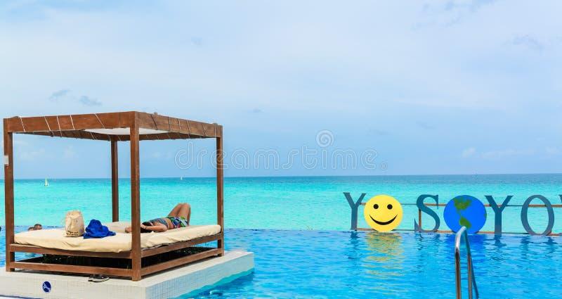 Γοητεύοντας, πανέμορφη άποψη της πισίνας που συγχωνεύει με τον ήρεμο ωκεανό, άνθρωποι που χαλαρώνει και που κολυμπά στοκ εικόνα