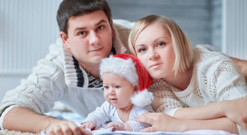 Γονείς και ένα χαριτωμένο μωρό σε ένα καπέλο Άγιου Βασίλη στοκ φωτογραφία με δικαίωμα ελεύθερης χρήσης