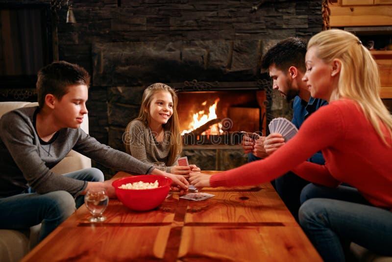 Γονείς και παιδιά οικογενειακού χρόνου που παίζουν τις κάρτες στο σπίτι στοκ εικόνες