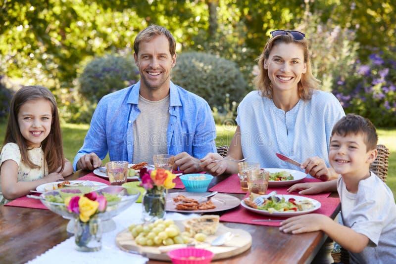 Γονείς και παιδιά που έχουν ένα μεσημεριανό γεύμα μαζί στον κήπο στοκ εικόνες