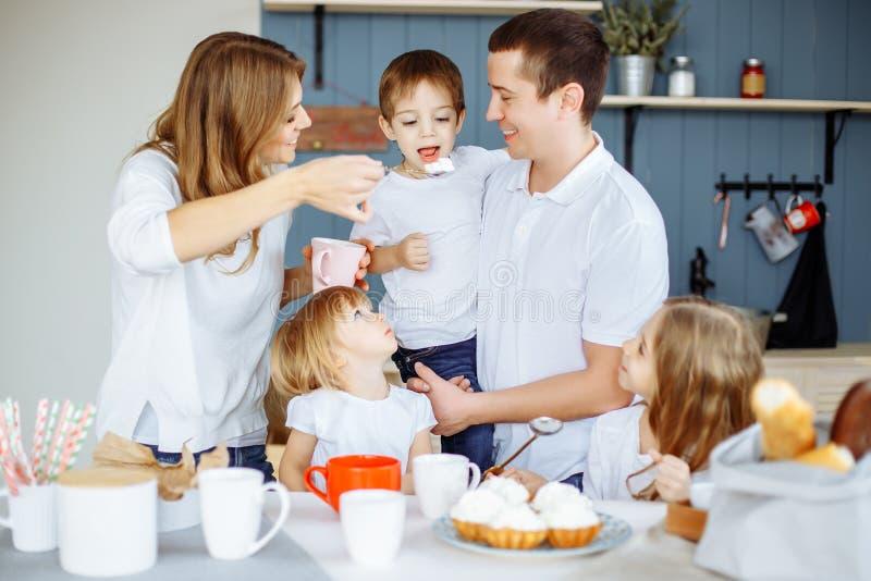 Γονείς και τρία παιδιά τους που στην κουζίνα και που απολαμβάνουν από κοινού στοκ φωτογραφίες με δικαίωμα ελεύθερης χρήσης