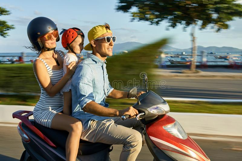 Γονείς με την οδηγώντας μοτοσικλέτα παιδιών τους στην ηλιόλουστη οδό πόλεων στοκ φωτογραφία