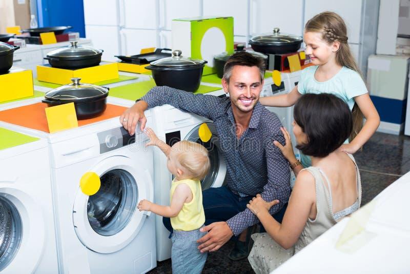 Γονείς με δύο παιδιά που επιλέγουν το πλυντήριο στην εγχώρια συσκευή στοκ φωτογραφίες με δικαίωμα ελεύθερης χρήσης