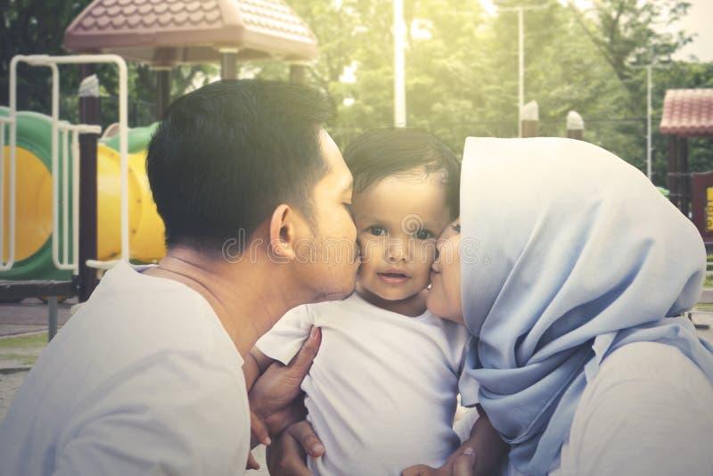 Γονείς που φιλούν την κόρη τους στην παιδική χαρά στοκ φωτογραφίες