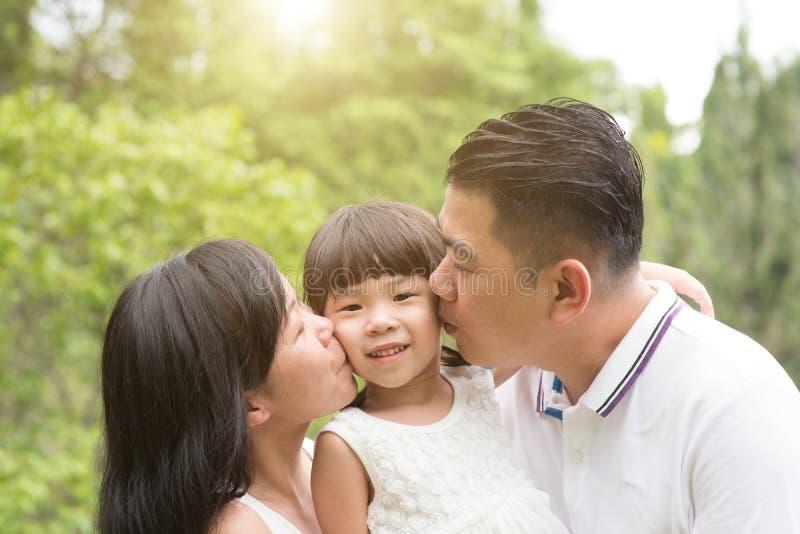 Γονείς που φιλούν το παιδί στο υπαίθριο πάρκο στοκ εικόνα με δικαίωμα ελεύθερης χρήσης