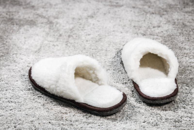 Γούνινο άσπρο χρώμα εγχώριων παντοφλών στον τάπητα στοκ φωτογραφία