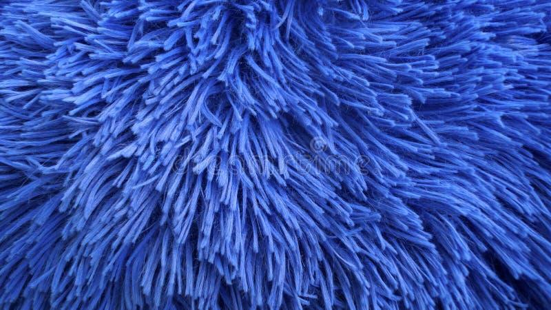 Γούνινο δασύτριχο κομμάτι μιας κάλυψης μαξιλαριών στο shinny μπλε ναυτικό χρώμα στοκ φωτογραφίες