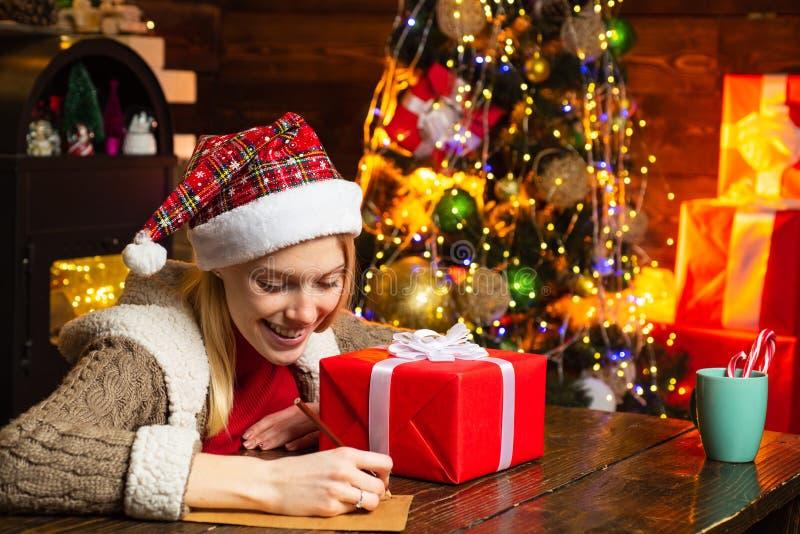 Γράφοντας επιστολή Ξύλινα εσωτερικά φω'τα γιρλαντών διακοσμήσεων Χριστουγέννων γυναικών Χριστουγεννιάτικο δέντρο Ευθυμία και αγάπ στοκ εικόνες με δικαίωμα ελεύθερης χρήσης