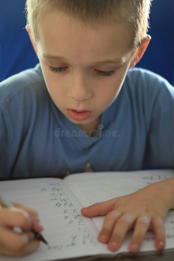 γράψιμο εργασίας αγοριών στοκ εικόνες