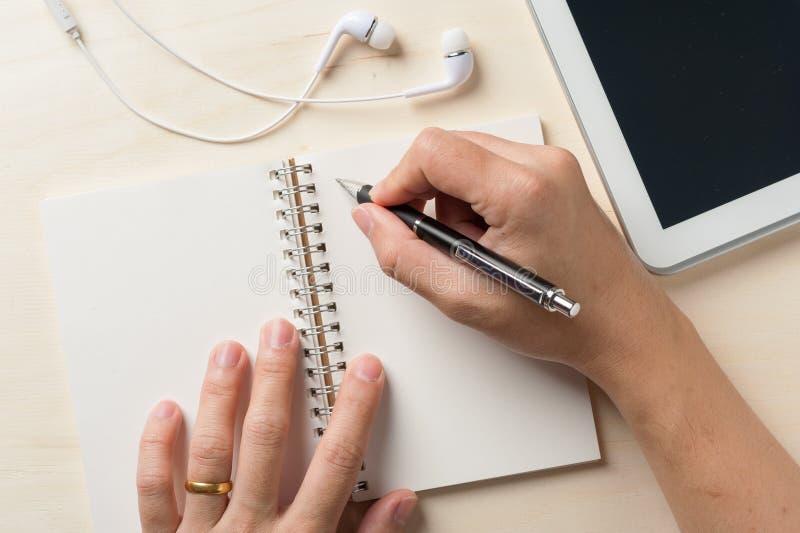 Γράψιμο στο σημειωματάριο με τη μικρή ταμπλέτα στοκ φωτογραφία με δικαίωμα ελεύθερης χρήσης