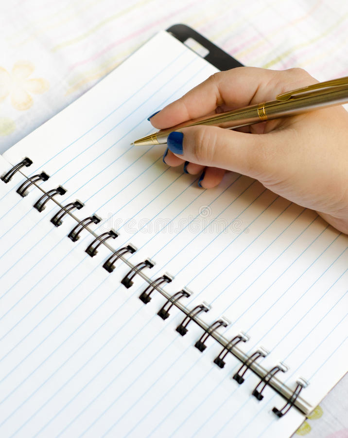 Γράψιμο στο σημειωματάριο στοκ εικόνα