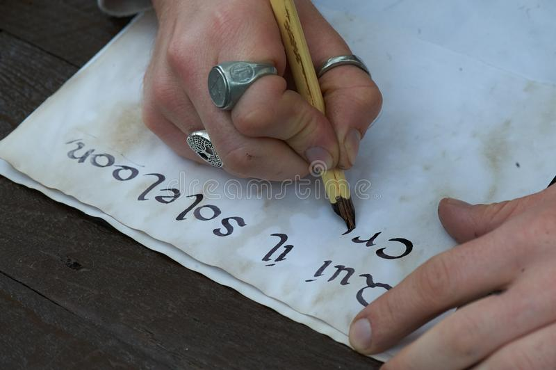 Γράψιμο των μανδρών καλλιγραφίας στο παλαιό κομμάτι χαρτί στοκ φωτογραφία με δικαίωμα ελεύθερης χρήσης