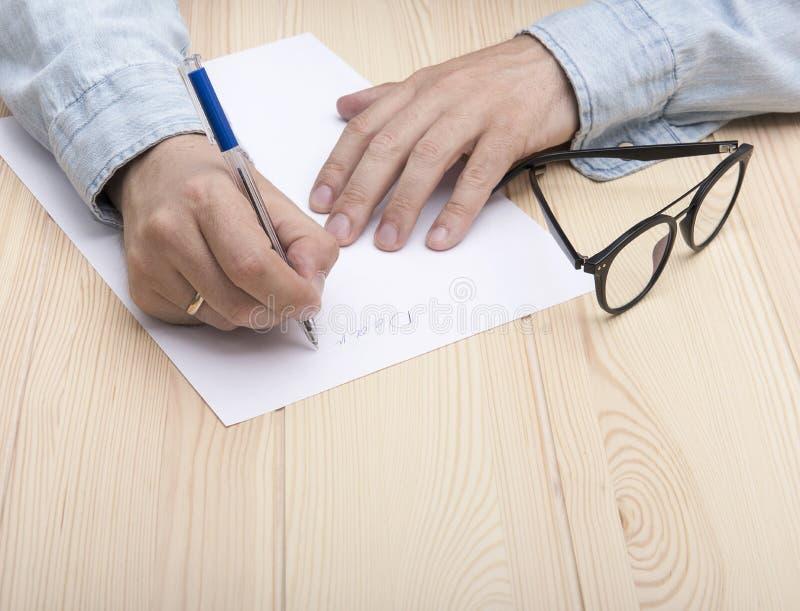 Γράψτε μια επιστολή Στα χέρια ενός ατόμου είναι μια μάνδρα ballpoint και γράφει μια επιστολή στοκ εικόνα