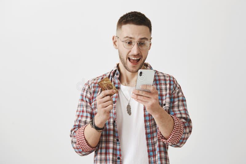 Γρήγορη και κατάλληλη τραπεζική έννοια Πορτρέτο του ευτυχούς και συγκλονισμένου ελκυστικού άνδρα σπουδαστή στην καθιερώνουσα τη μ στοκ φωτογραφία
