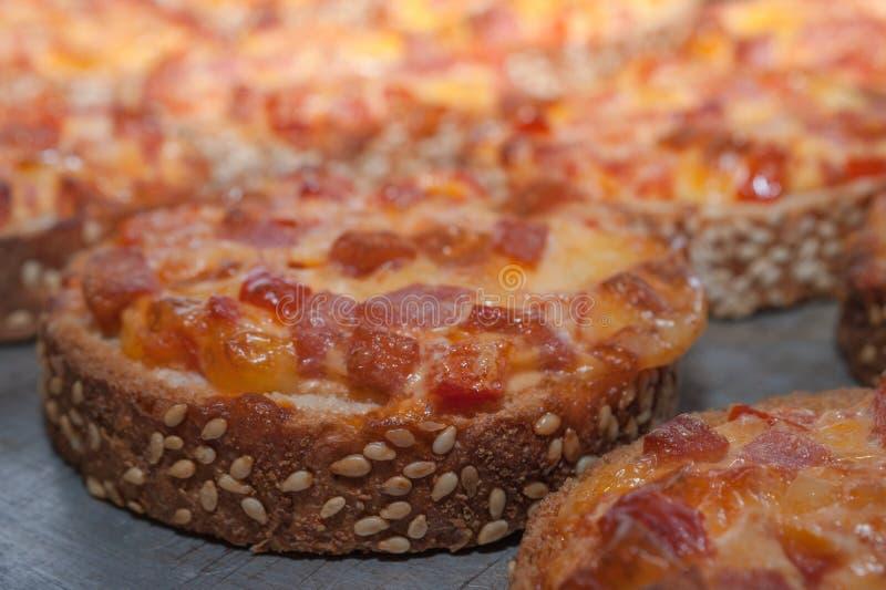Γρήγορο πρόχειρο φαγητό Ψωμί σουσαμιού που ψήνεται με το σαλάμι και το τυρί στο δίσκο φούρνων Μίνι πίτσα στοκ φωτογραφίες με δικαίωμα ελεύθερης χρήσης