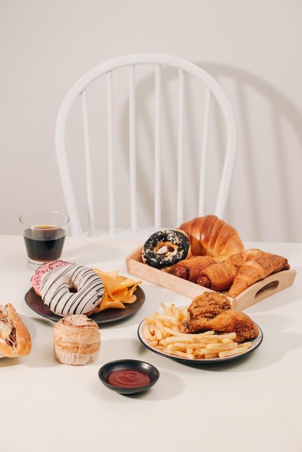 Γρήγορο φαγητό και ανθυγειινή έννοια κατανάλωσης - κλείστε επάνω του χάμπουργκερ ή cheeseburger, τσιγαρισμένα δαχτυλίδια καλαμαρι στοκ εικόνες με δικαίωμα ελεύθερης χρήσης
