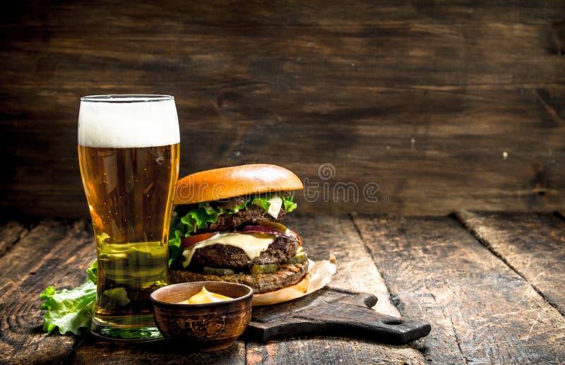 Γρήγορο φαγητό Μεγάλο burger με το βόειο κρέας και ένα ποτήρι της μπύρας στοκ φωτογραφίες