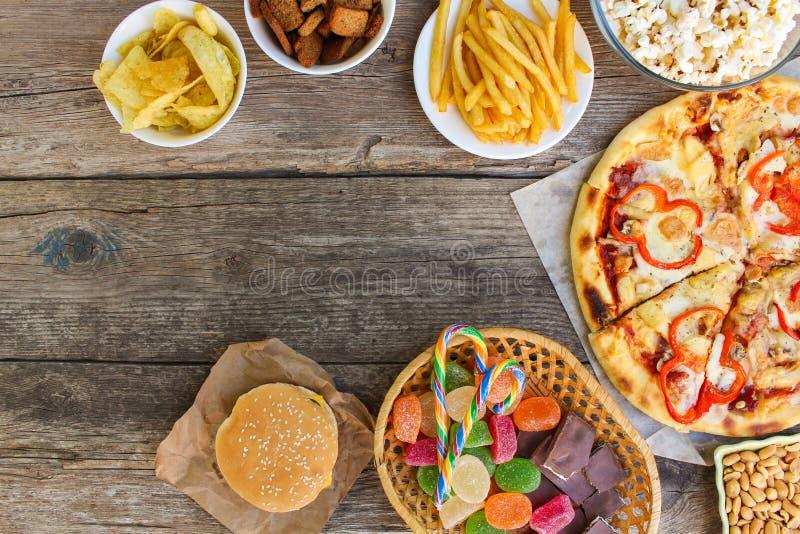 Γρήγορο φαγητό στο παλαιό ξύλινο υπόβαθρο Έννοια της κατανάλωσης παλιοπραγμάτων στοκ φωτογραφίες