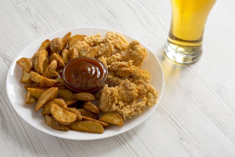 Γρήγορο φαγητό: τηγανισμένες σφήνες πατατών, δαγκώματα κοτόπουλου σε μια άσπρη σάλτσα πιάτων, μπύρας και σχαρών σε έναν άσπρο ξύλ στοκ εικόνες με δικαίωμα ελεύθερης χρήσης