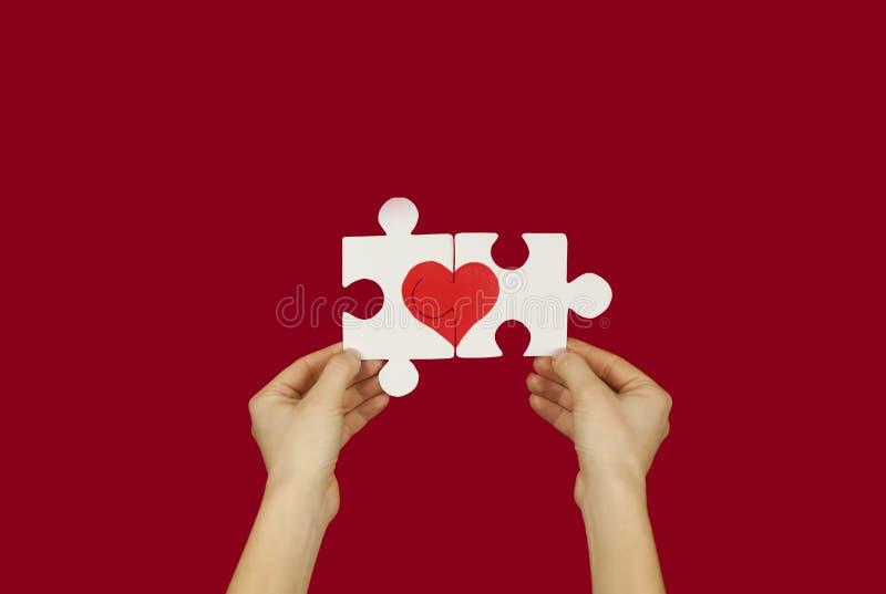 Γρίφος με μια κόκκινη καρδιά στα χέρια ενός αγαπώντας ζεύγους Έννοια ημέρας βαλεντίνων ` s Σε ένα απομονωμένο υπόβαθρο στοκ εικόνες