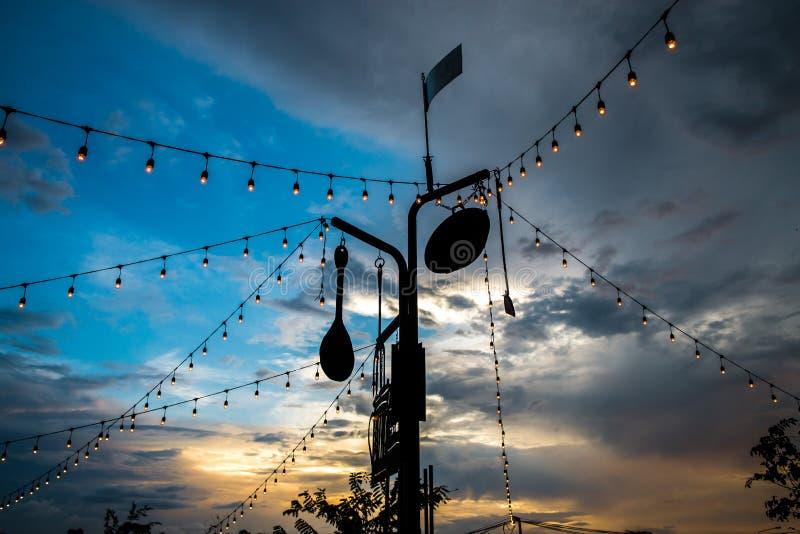 Γραμμή εορταστικών διακοσμήσεων φω'των στο εστιατόριο με το υπόβαθρο ουρανού λυκόφατος στοκ εικόνες