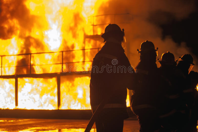 Γραμμή πυροσβεστών που στέκονται με τη μάνικα μπροστά από μια καίγοντας δομή κατά τη διάρκεια της πυροσβεστικής άσκησης στοκ φωτογραφία με δικαίωμα ελεύθερης χρήσης