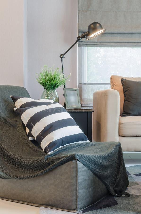 Γραπτά μαξιλάρια στο μαύρο καναπέ με το σύγχρονο λαμπτήρα στον πίνακα στοκ εικόνα με δικαίωμα ελεύθερης χρήσης