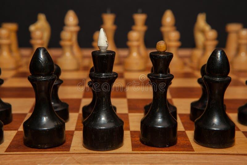 Γραπτά ξύλινα κομμάτια σκακιού εν πλω με το μαύρο υπόβαθρο στοκ εικόνες