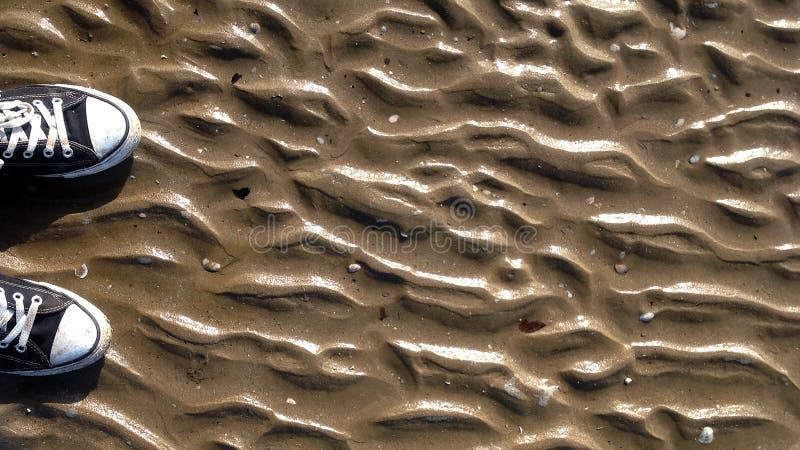 Γραπτά πάνινα παπούτσια στο υπόβαθρο άμμου για το σχέδιό σας στοκ φωτογραφία