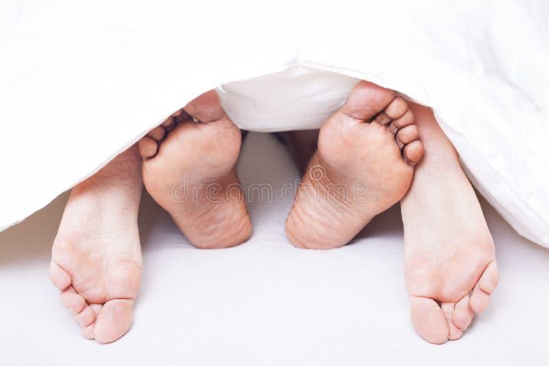 Γραπτά πόδια του διαφυλετικού ζεύγους στο κρεβάτι στοκ φωτογραφίες με δικαίωμα ελεύθερης χρήσης