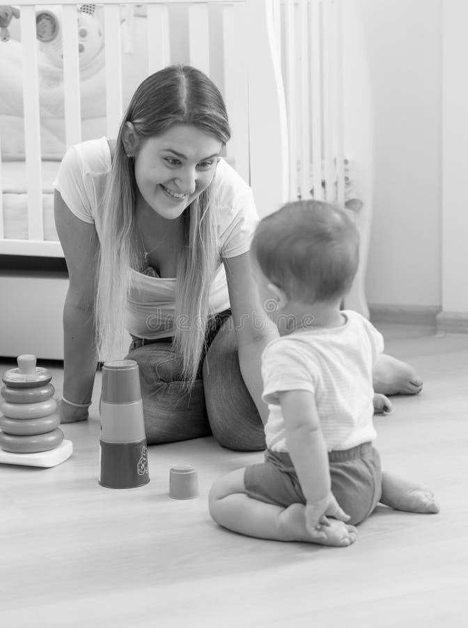 Γραπτή φωτογραφία της όμορφης νέας συνεδρίασης μητέρων στο πάτωμα και του χαμόγελου στο γιο μωρών της στοκ φωτογραφία με δικαίωμα ελεύθερης χρήσης