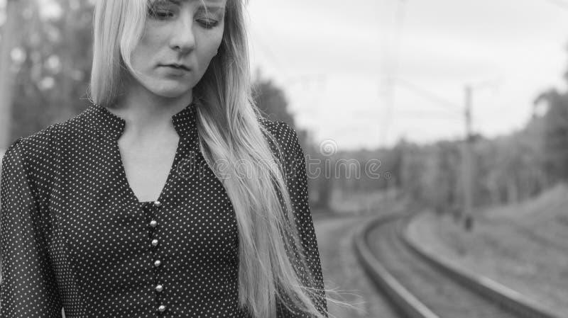 γραπτό πορτρέτο μιας νέας ξανθής γυναίκας με μακρυμάλλη σε ένα ντεμοντέ φόρεμα, που στέκεται με ένα λυπημένο στοχαστικό expressi στοκ εικόνες