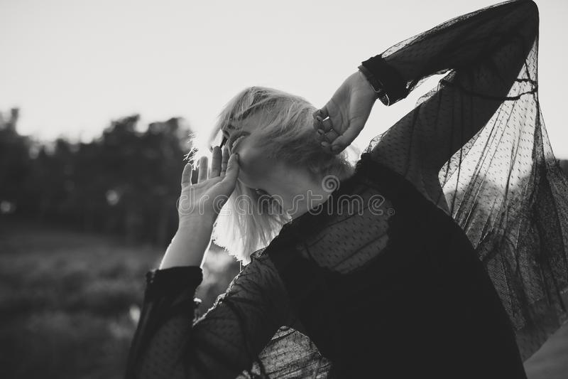 Γραπτό πορτρέτο της νέας γυναίκας με την ξανθή τρίχα και των γυαλιών ηλίου υπαίθρια στη φύση χορεύοντας στοκ εικόνες
