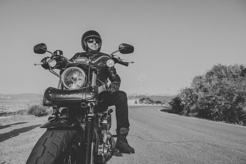 Γραπτό πορτρέτο του ατόμου με το μαύρα κράνος, το σακάκι και τα γυαλιά ηλίου που στέκονται σε μια κλασική αμερικανική μοτοσικλέτα στοκ εικόνα