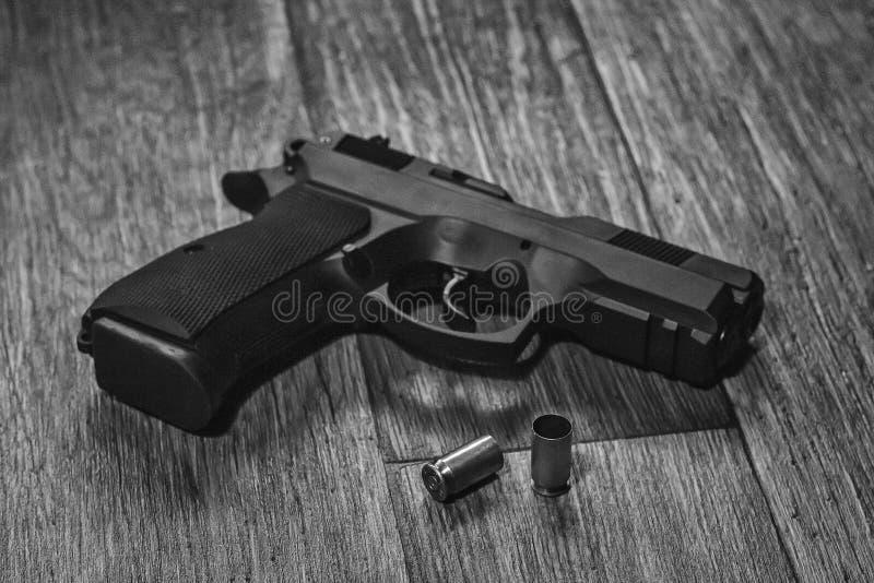 Γραπτό πυροβόλο όπλο που βρίσκεται στο έδαφος με τα κοχύλια στοκ φωτογραφία με δικαίωμα ελεύθερης χρήσης