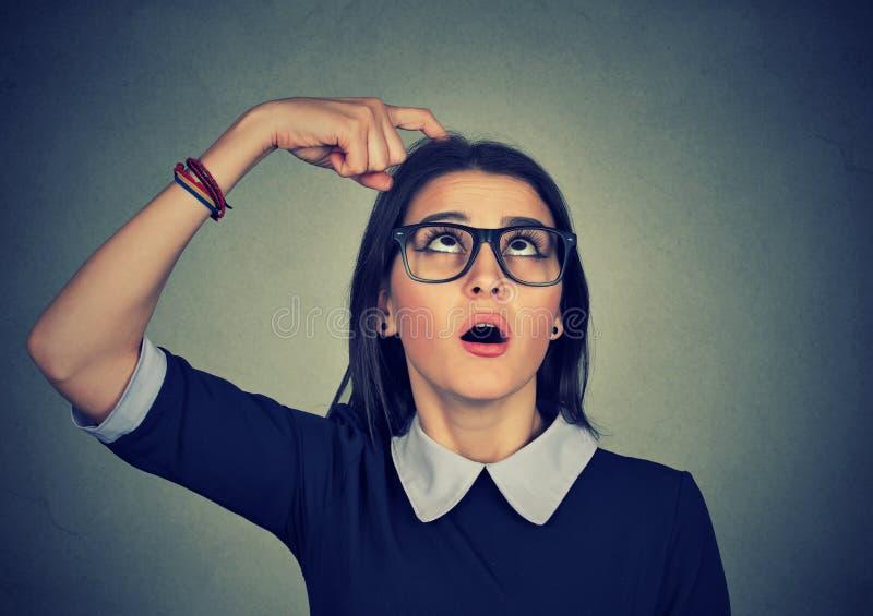 Γρατσουνίζοντας κεφάλι γυναικών που σκέφτεται για κάτι που φαίνεται επάνω προσπαθώντας σε recal στοκ εικόνες