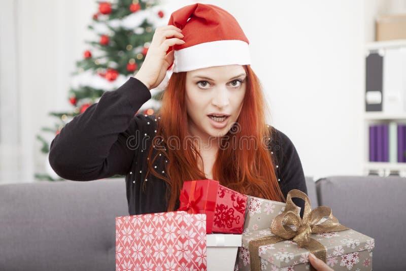 Γρατσουνίζοντας κεφάλι κοριτσιών και κράτημα των δώρων Χριστουγέννων στοκ εικόνες