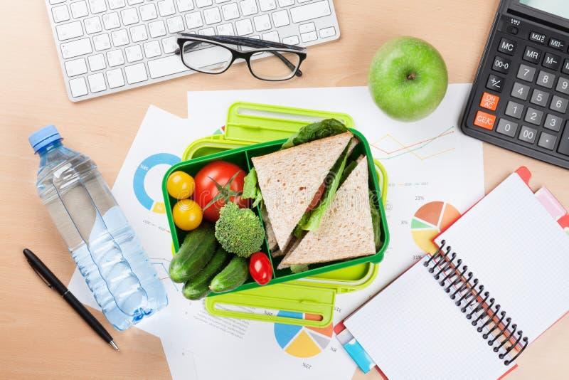 Γραφείο γραφείων με τις προμήθειες και το καλαθάκι με φαγητό στοκ φωτογραφία με δικαίωμα ελεύθερης χρήσης