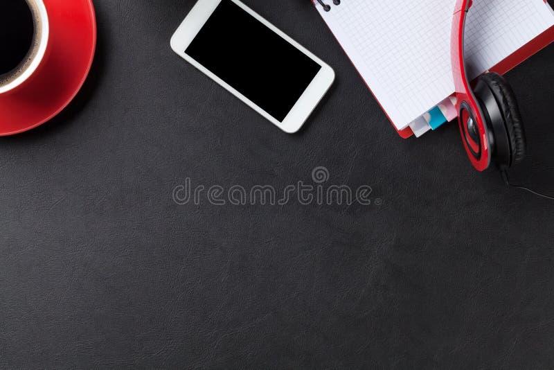 Γραφείο με το σημειωματάριο, τον καφέ, το smartphone και τα ακουστικά στοκ εικόνα