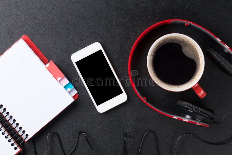 Γραφείο με το σημειωματάριο, τον καφέ, το smartphone και τα ακουστικά στοκ φωτογραφία